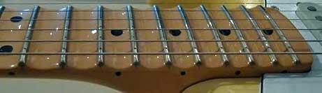 Bildet er lånt av Michael919 fra Strat Talk Forum, og viser en stratocaster med høy bånd-krone og skallopert gripebrett
